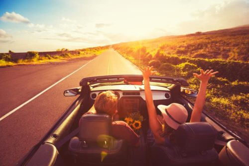 Cabriofahrt in der Wüste. 2 Personen. Beifahrerin mit Hut hebt die Arme