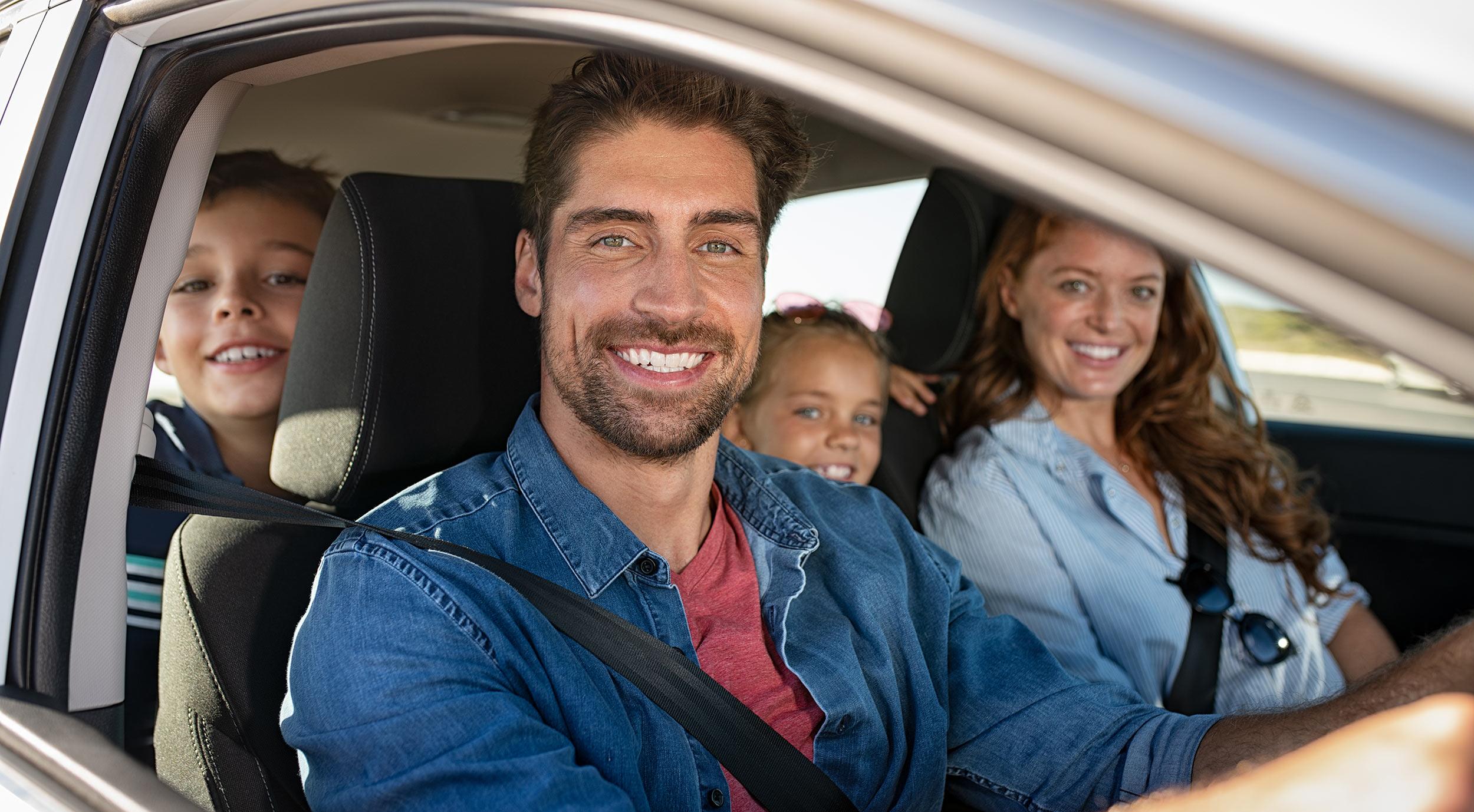 Familie lachend in einen Auto. Vorne: Frau und Mann. Hinten zwei Kinder (Junge und Mädchen)